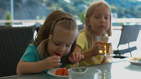 Zwei kleine Schwestern, die im Café essen Stockbilder