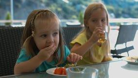 Zwei kleine Schwestern, die im Café essen Lizenzfreie Stockfotografie