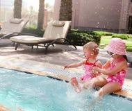 Zwei kleine Schwestern, die im Swimmingpool spielen Lizenzfreie Stockbilder