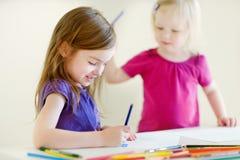 Zwei kleine Schwestern, die mit bunten Bleistiften zeichnen Stockfotos