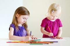 Zwei kleine Schwestern, die mit bunten Bleistiften zeichnen Stockbild