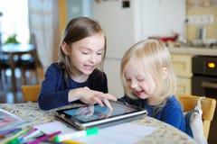 Zwei kleine Schwestern, die mit einer digitalen Tablette spielen Lizenzfreies Stockfoto