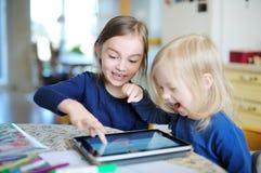 Zwei kleine Schwestern, die mit einer digitalen Tablette spielen Stockbild