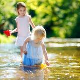 Zwei kleine Schwestern, die mit Papierbooten spielen Lizenzfreie Stockfotos