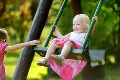 Zwei kleine Schwestern, die Spaß auf einem Schwingen haben Lizenzfreies Stockbild
