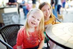 Zwei kleine Schwestern, die Spaß in einem Café im Freien haben Stockfotografie