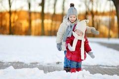 Zwei kleine Schwestern, die Spaß am Tag des verschneiten Winters haben Stockfoto