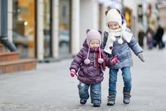 Zwei kleine Schwestern, die Spaß am Wintertag haben Lizenzfreie Stockbilder