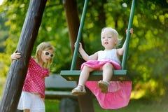 Zwei kleine Schwestern, die Spaß auf einem Schwingen haben Stockfotos