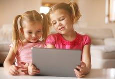 Zwei kleine Schwestern, die Tablette verwenden Porträt Lizenzfreie Stockbilder