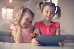 Zwei kleine Schwestern, die Tablette verwenden Porträt Lizenzfreie Stockfotografie