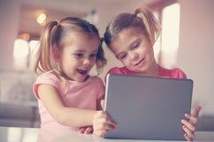 Zwei kleine Schwestern, die Tablette verwenden Spielerische Zeit für Schwestern Stockfotografie