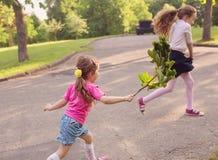 Zwei kleine Schwestern laufen gelassen und Spiel auf der Straße im Park auf einem Krieg Stockfoto