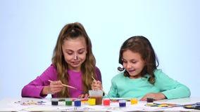 Zwei kleine Schwestern malen ein Bild und fangen an, auf das Gesicht zu zeichnen Abschluss oben Weißer Hintergrund stock footage