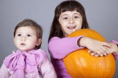 Zwei kleine Schwestern mit Kürbis Lizenzfreies Stockfoto