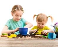 Zwei kleine Schwestern nehmen an der Gartenarbeit teil Lizenzfreie Stockfotografie