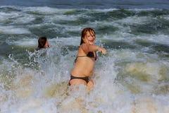 zwei kleine Schwestern schwimmen im Ozean Stockbild
