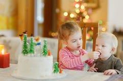 Zwei kleine Schwestern und ein Weihnachtskuchen Lizenzfreie Stockbilder