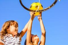 Zwei kleine sieben jährige Mädchen, die draußen Basketball spielen Lizenzfreies Stockbild