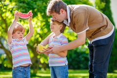 Zwei kleine Vorschulkinderjungen und -vater, die Wassermelone essen Lizenzfreie Stockfotos
