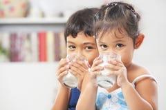 Zwei kleiner Junge und Trinkmilch des Mädchens lizenzfreie stockbilder