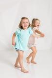 Zwei kleines lustiges und lachendes Mädchen in der identischen Kleidung von den verschiedenen Farben, die im weißen Studio spiele Lizenzfreie Stockfotografie