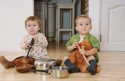 Zwei Kleinkinder der Junge und Mädchen, die auf der Küche sitzen, breiten playin aus Lizenzfreie Stockfotografie