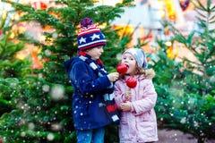 Zwei Kleinkinder, die crystalized Apfel auf Weihnachtsmarkt essen Stockfoto