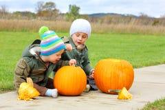 Zwei Kleinkinder, die Kürbise schnitzen Lizenzfreie Stockfotos
