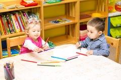 Zwei Kleinkinder, die mit bunten Bleistiften in der Vorschule am Tisch zeichnen Lizenzfreie Stockfotos
