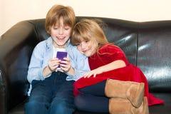 Zwei Kleinkinder, die mit einem Handy spielen Lizenzfreies Stockfoto