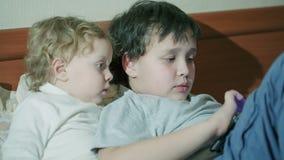 Zwei Kleinkinder, die mit einer Tablette spielen stock video footage