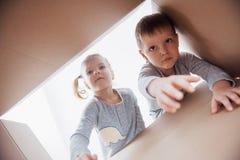 Zwei Kleinkinder Junge und Mädchenöffnungspappschachtel und nach innen schauen mit Überraschung lizenzfreie stockbilder