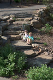 Zwei Kleinkinder stehen still, während sie an einem allgemeinen Garten erforschen Stockbild
