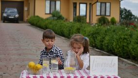 Zwei Kleinkinder verkaufen Limonade auf einem selbst gemachten Limonadestand an einem sonnigen Tag mit einem Preiszeichen für ein Stockbilder