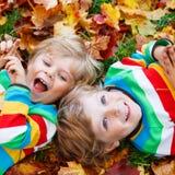 Zwei Kleinkindjungen, die in Herbstlaub in der bunten Kleidung legen Stockfotos