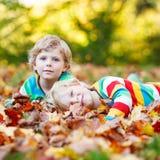Zwei Kleinkindjungen, die in Herbstlaub in der bunten Kleidung legen Lizenzfreie Stockfotografie