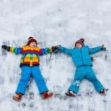 Zwei Kleinkindjungen, die Schneeengel im Winter, draußen machen Stockfotografie