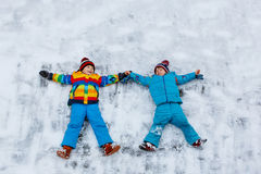 Zwei Kleinkindjungen, die Schneeengel im Winter machen Stockfotos