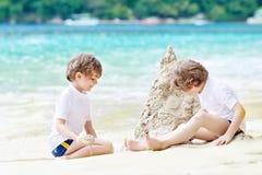 Zwei Kleinkindjungen, die Spaß mit dem Errichten eines Sandburgs auf tropischem Strand von Seychellen haben Kinder, die zusammen  lizenzfreie stockfotografie