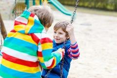 Zwei Kleinkindjungen, die Spaß mit Kettenschwingen auf Spielplatz im Freien haben Lizenzfreie Stockbilder