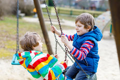 Zwei Kleinkindjungen, die Spaß mit Kettenschwingen auf Spielplatz im Freien haben Stockbild