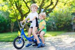 Zwei Kleinkindjungen, die zusammen mit Fahrrad reiten Lizenzfreies Stockbild