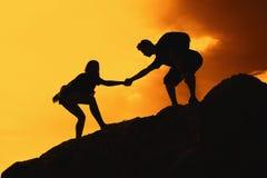 Zwei kletternde Leute in den Bergen als Symbol für Hilfe und Erfolg stockbilder