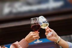 Zwei klirrende Gläser der Leute mit Rot und Weißwein Lizenzfreie Stockfotos