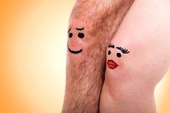 Zwei Knie mit Gesichtern vor gelbem Hintergrund Lizenzfreie Stockfotos