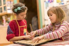 Zwei Kochingwer-Kekse der Schwestern 7 und 5 Jahre alte Verbreiten Sie den Teig auf einem Messingarbeiter Zwei Mutter ` s Assiste Stockfoto