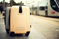 Zwei Koffer, die auf Bahnhof gegen Stadt stehen, bilden aus Ferien und Reisekonzept Citypass-Licht-Schiene herein stockfotos