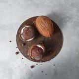 Zwei Kokosnusshälften mit gefrorener frischer Eiscreme und ganzer Kokosnuss auf einem runden hölzernen Brett auf einer grauen Ste stockfotografie