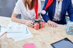 Zwei Kollegeaustausch Weihnachtsgeschenke inside lizenzfreies stockbild